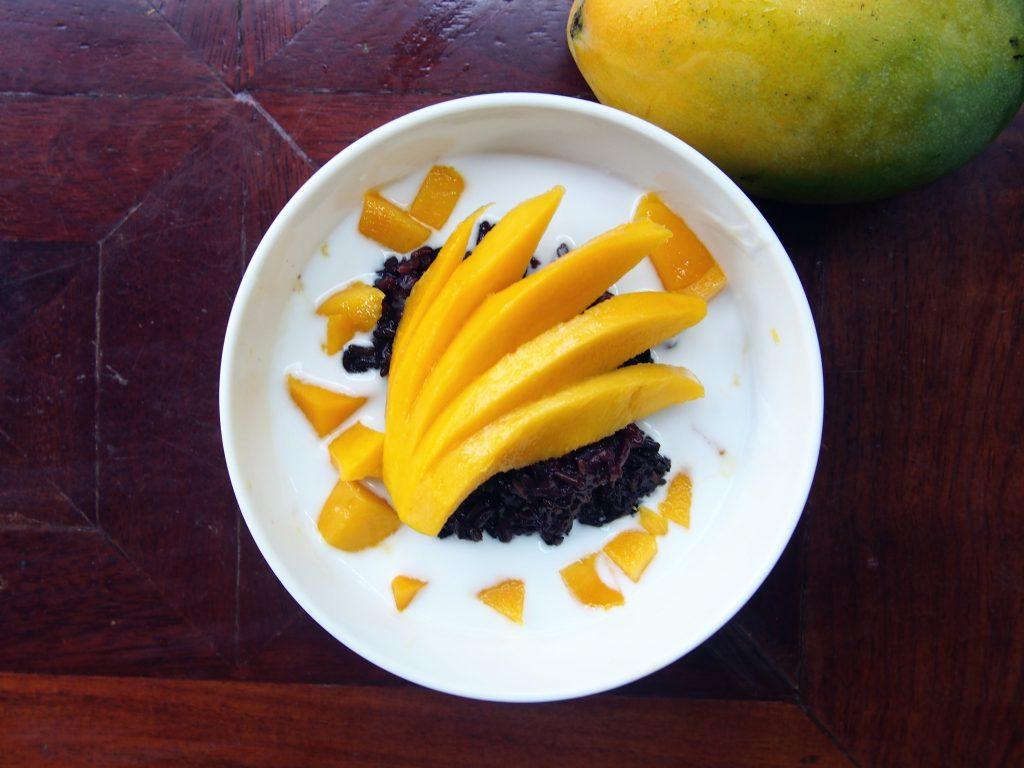 Coconut milk over black sticky rice with Mango